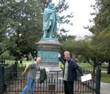 Colleagues pose next to statue during our GeoTrek team building activity in Rhode Island
