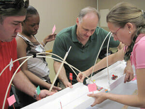 a team merges their bridge halves during our Build a Bridge team building activity