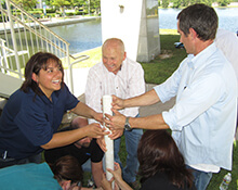 Team strategizes on how to keep dry during the Leaky Pipe team building activity in Woodlands Texas